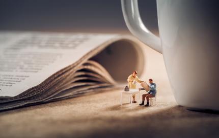 Kleine mensjes bij een krant en een kop koffie